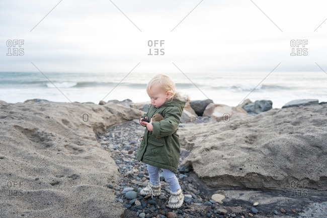 Child exploring on cold weather beach