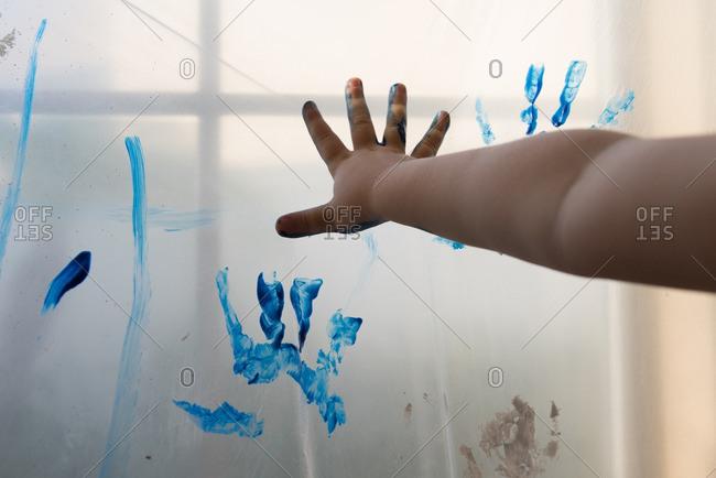 Child making handprint on plastic sheet
