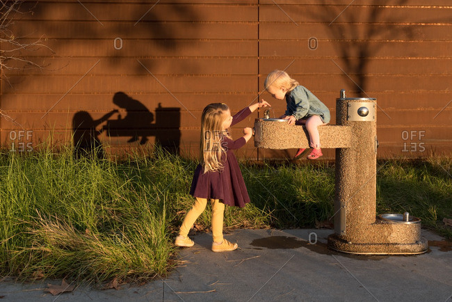 Girls playing around a water fountain