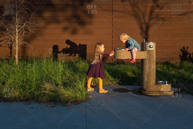 Girls playing around water fountain