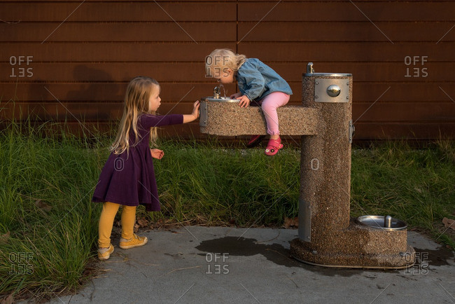 Girls playing around drinking fountain
