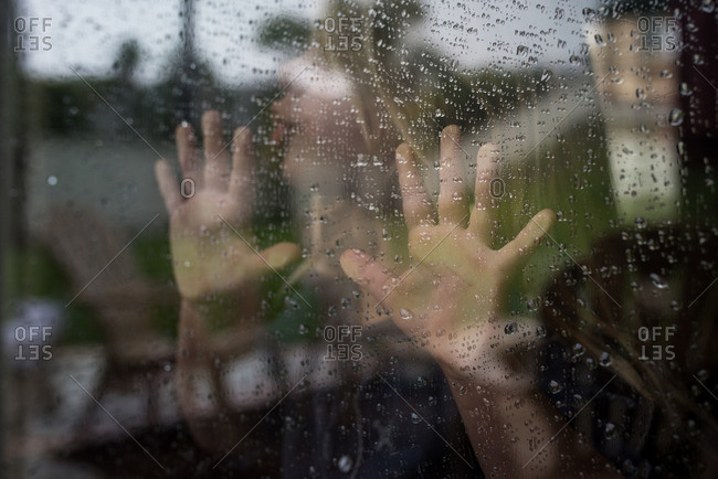 Girl's hands on a rainy window