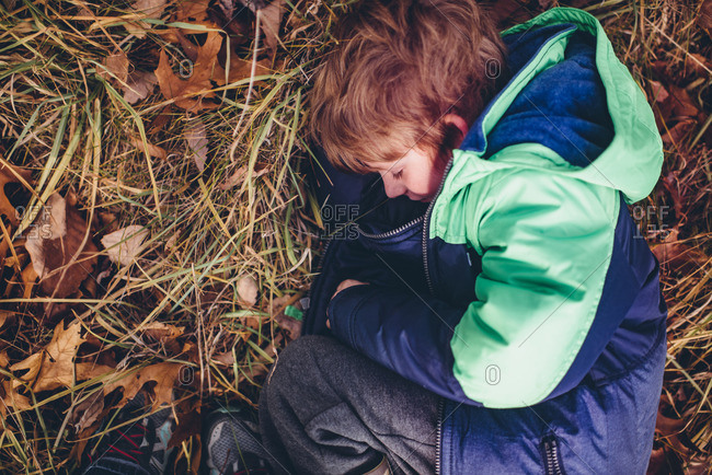 Little boy in a jacket curled up in leaves and grass