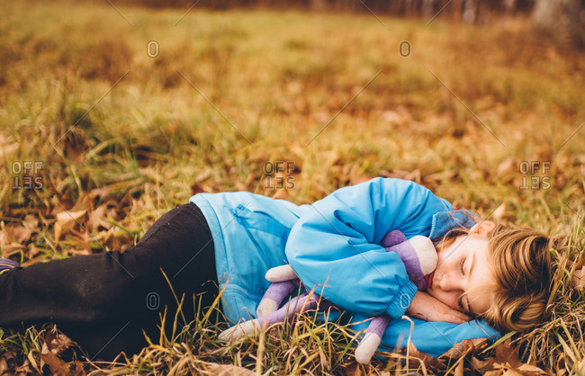Little girl lying in a field with a stuffed monkey