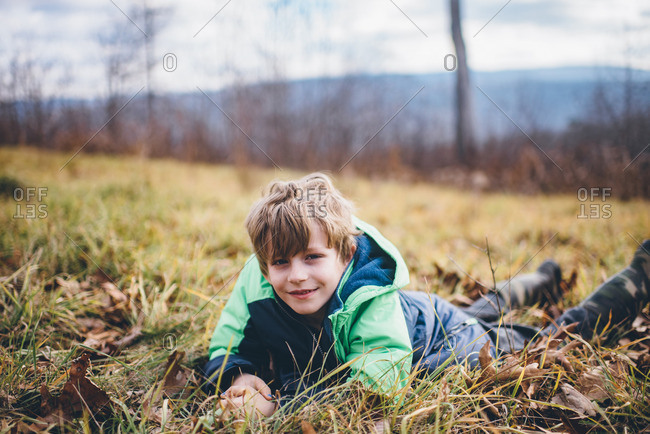 Boy lying on his stomach in a grassy field