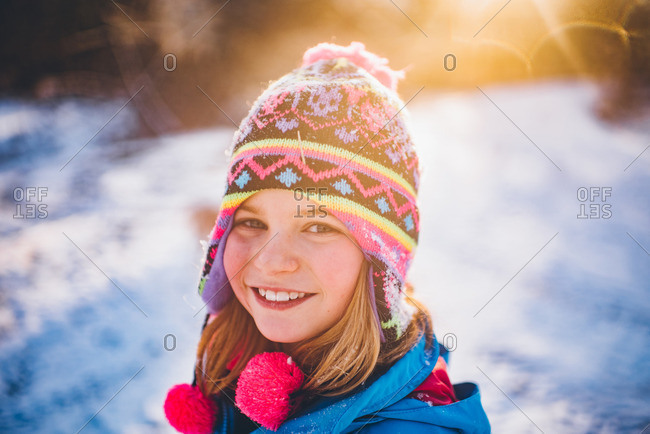 Little girl in a toboggan standing in the snow
