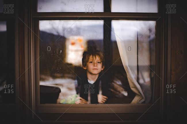 Little boy looking out the window of a house