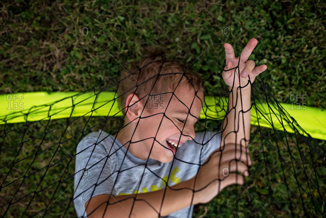 Little boy lying on ground tangled in a net