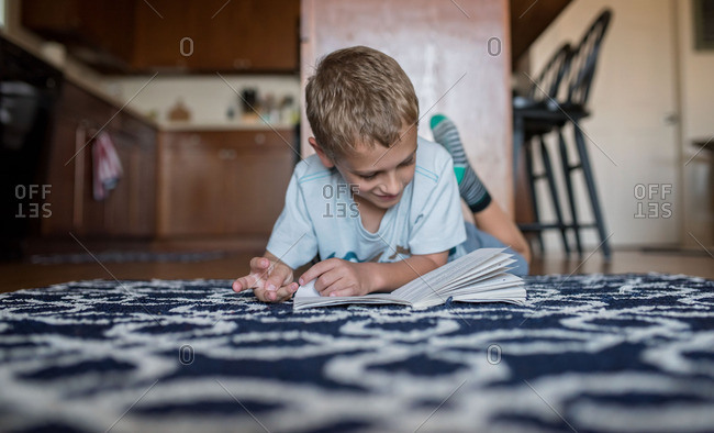 Boy lying on floor reading a book