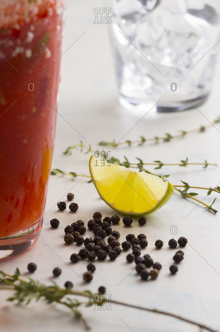 Peppercorn, lime and thyme beside a bloody Mary cocktail