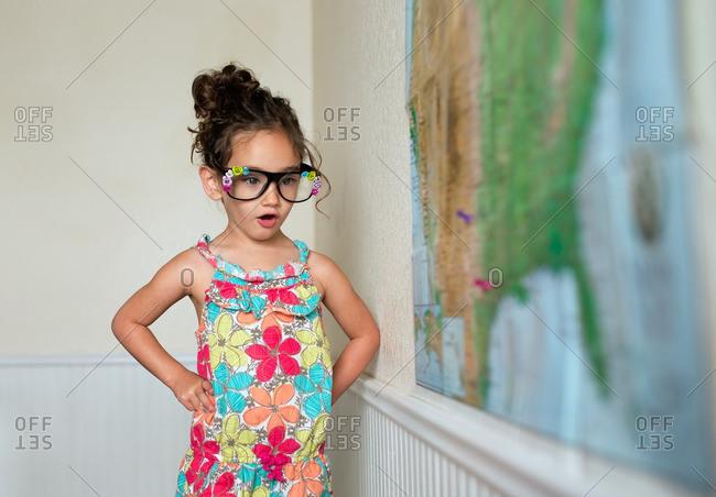 Little girl by a map pretending to be a teacher