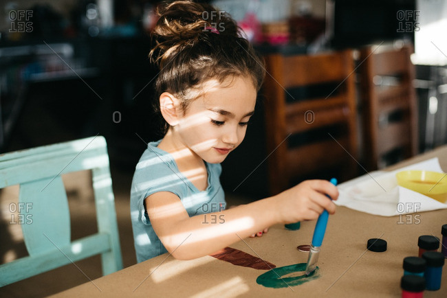 Little girl painting a tree
