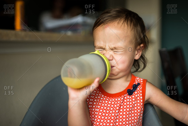 Toddler girl making sour face while sipping on a juice cup