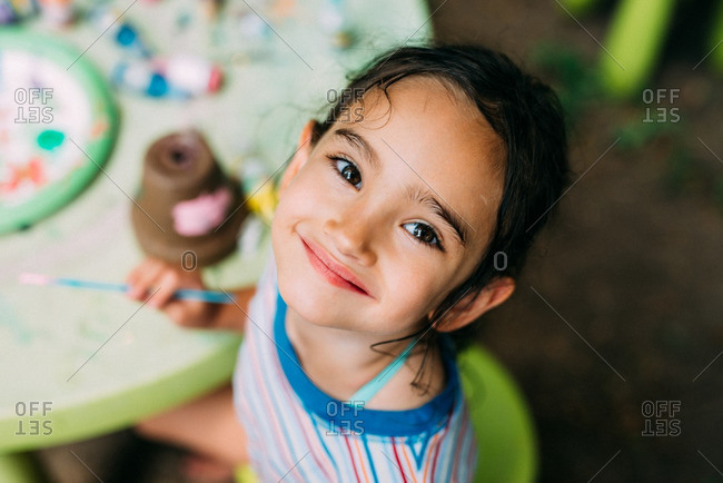 Little girl painting and smiling outdoors