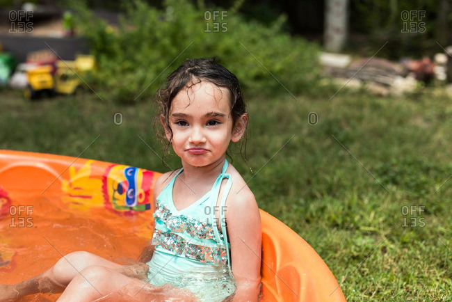 Little girl sitting in a child's orange swimming pool