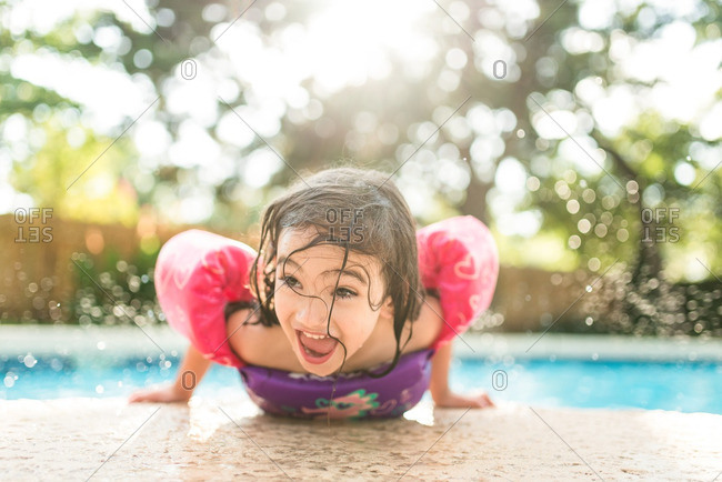 Little girl kicking her feet on the edge of a swimming pool