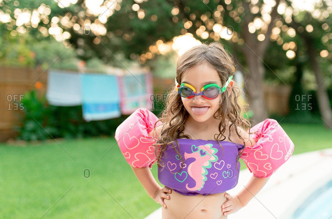 Little girl wearing colorful floatation device and goggles making silly face