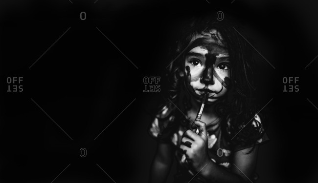 Little girl painting her face in black and white