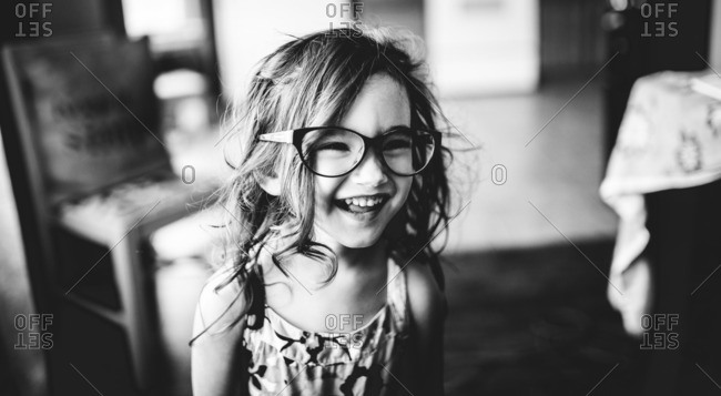 Young girl wearing glasses and smiling in black and white
