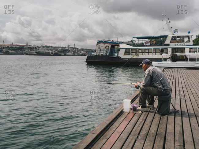 Simferopol, Crimea - January 24, 2017: Old man fishing on the coast of Simferopol