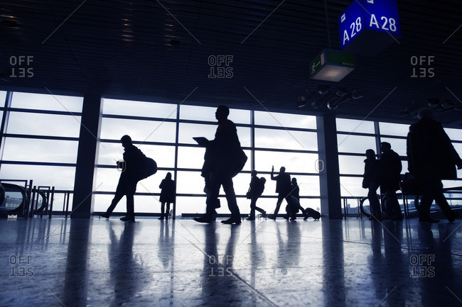 People walking in front of windows at an airport terminal