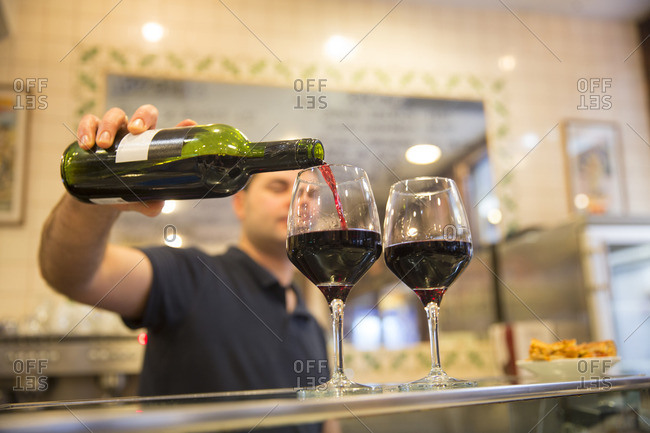 Man pouring two glasses of wine in a tapas bar