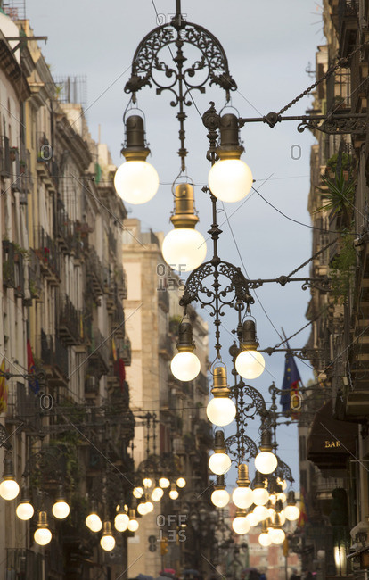 Ornate wrought iron street lamps hanging over the streets of Barcelona