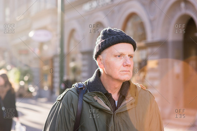 Portrait of senior man wearing a knit hat and jacket walking outside