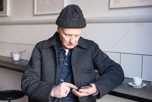 Senior man sitting at counter using his smartphone