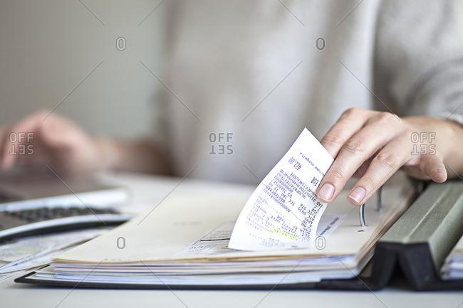 Woman going through receipts to record expenses