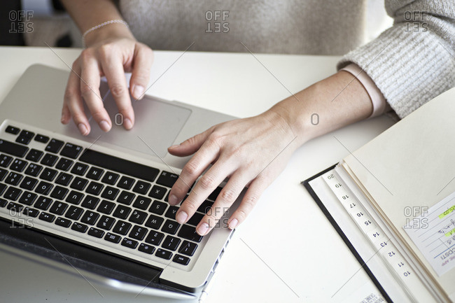 Overhead of woman working at laptop computer