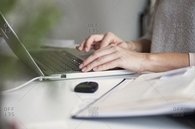 Close-up of woman's hands typing on computer
