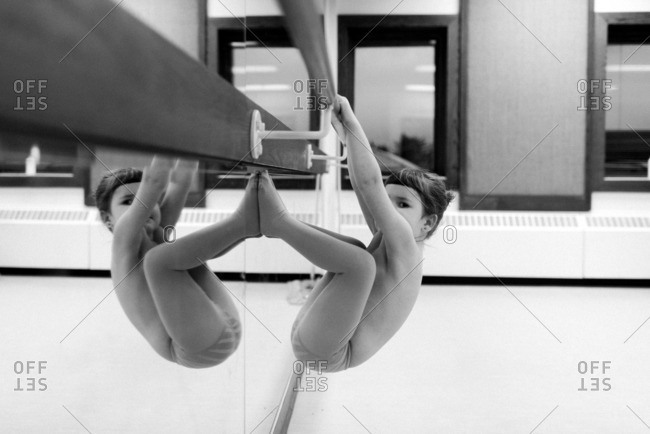 Young girl hanging on a ballet barre in dance class