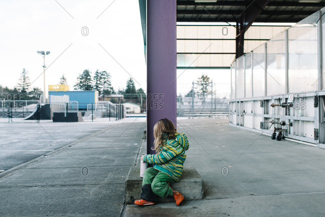 Young girl in green snow gear sitting next to pillar at public ice rink
