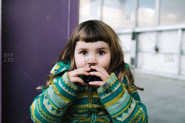 Close-up of young girl in green coat drinking from a cup