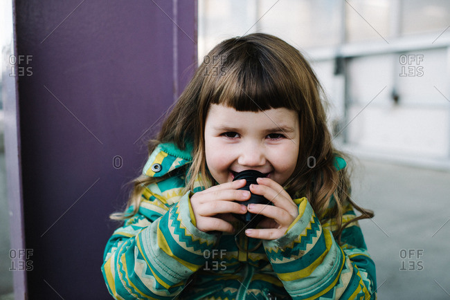 Close-up of laughing young girl drinking from a sport bottle lid