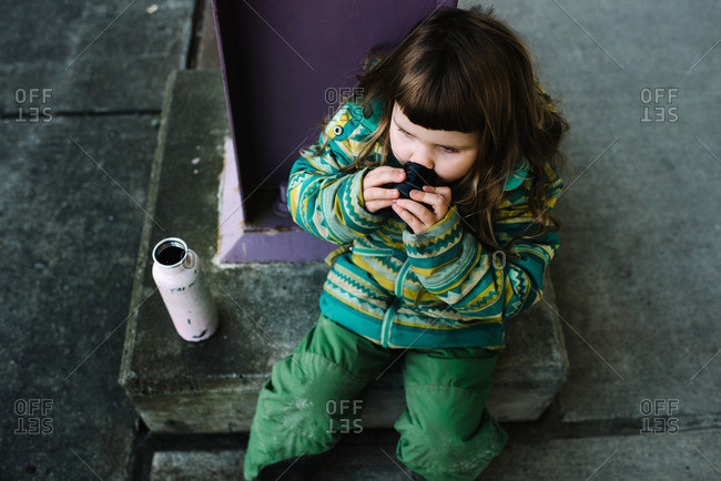Elevated view of young girl taking a drink from the lid of a sport bottle