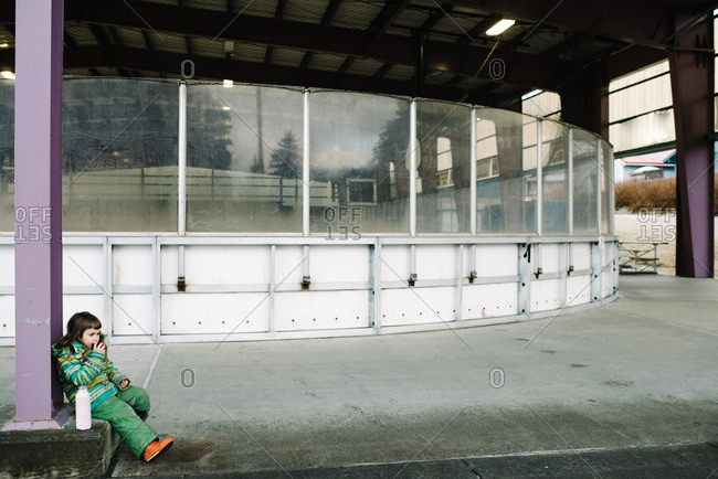 Girl sitting next to pillar at an ice rink