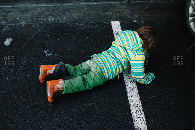 Young girl lying down in parking lot