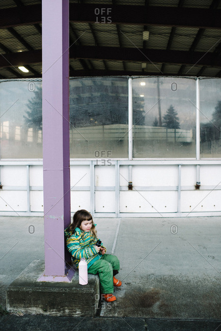 Young girl taking a break with her water bottle at ice rink