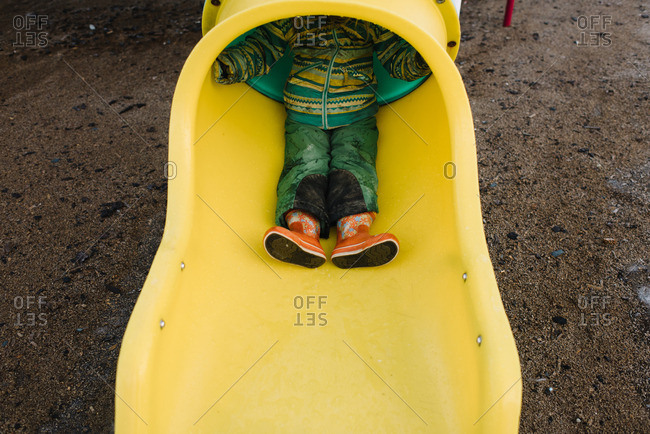 Child's feet in orange boots coming out of a tunnel slide