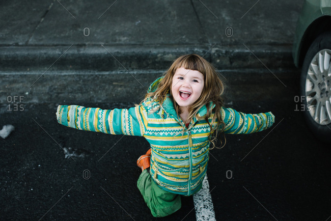 Happy young girl in green snow gear playing in parking lot