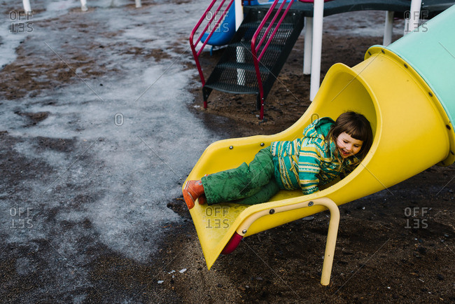 Young girl bundled in snow gear playing on slide