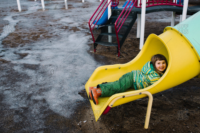 Young girl playing on slide in winter