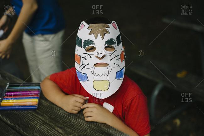 Little boy wearing paper tiger mask