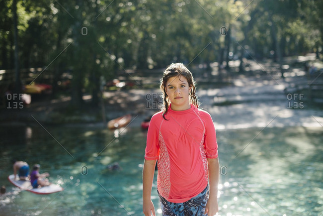 Portrait of a girl wearing pink swim shirt by a river