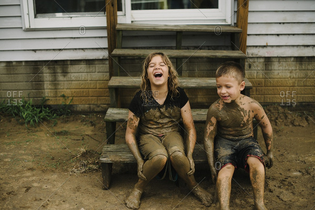 Two kids sitting on steps covered in mud