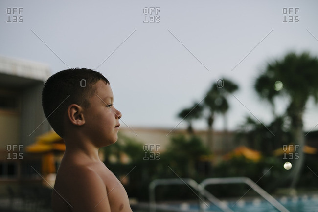 Boy standing outside by a swimming pool