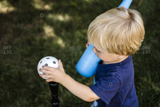 High angle view of boy playing t-ball in backyard