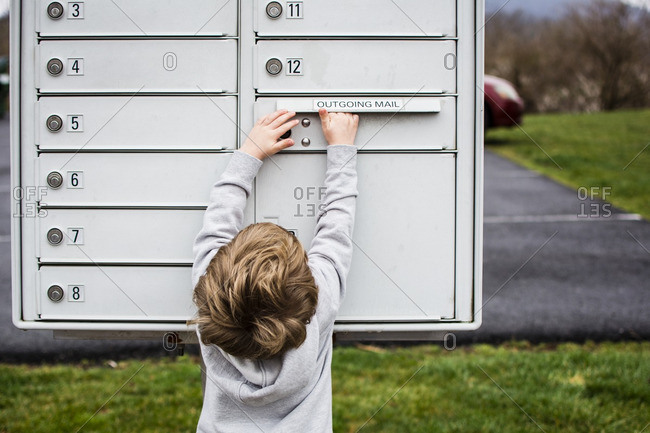 Rear view of boy removing letter from mailbox